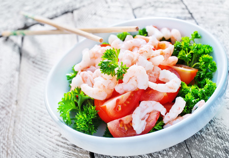 shrimp cocktail: salad with shrimps in bowls and on a table