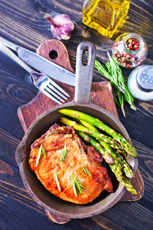 fried meat with asparagus in the pan photo