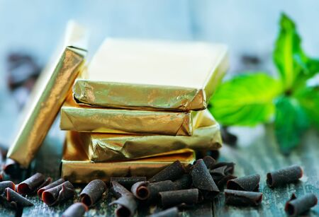 endorphines: chocolate candy with mint leaf on the wooden table