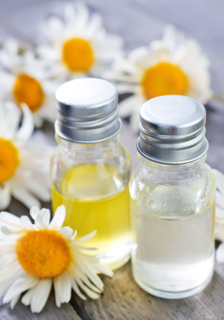 bath supplement: camomille oil in glass bottle and on a table