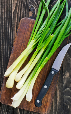 cebolla: cebolla verde sobre tabla y sobre una mesa Foto de archivo
