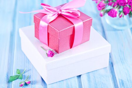 romance bed: box for present and flowers on a table