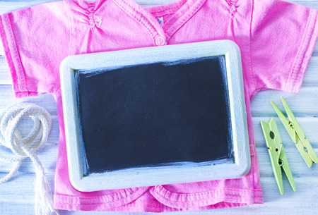baby clothes and black board on a table photo