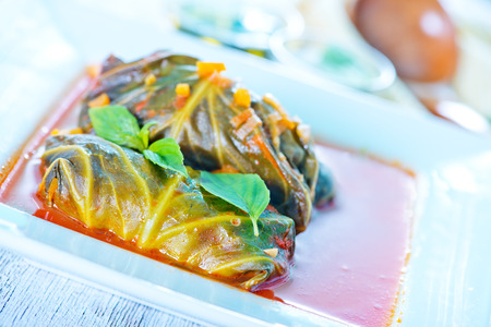 grecian: dolma with tomato sauce in the white bowl