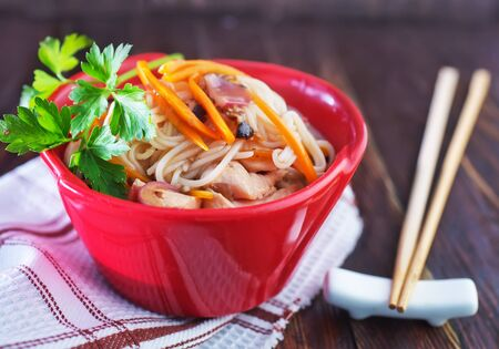 china cuisine: rice noodles with meat and vegetables in bowl