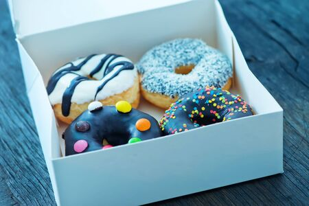 donuts in white box and on a table photo