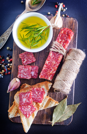 vespers: salami and toasts on the wooden board