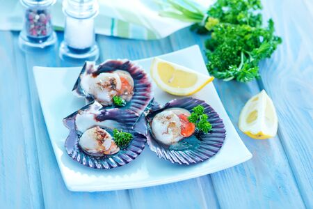half dressed: scallop with caviar and lemon juice on a table