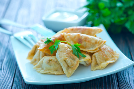 potstickers: fried dumplings on the white plate and on a table