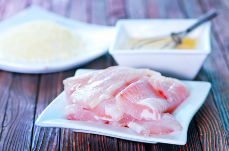 greenfish: flour, raw egg and raw fish on a table