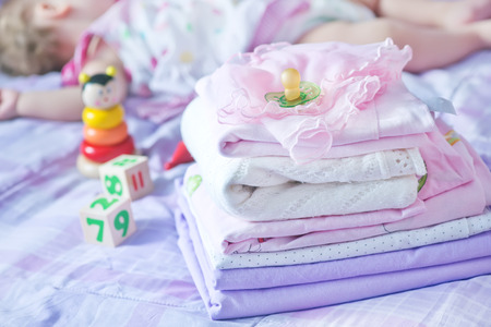 bedstead: baby clothes on the bed, color baby linen