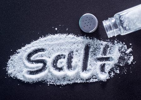 белый морской соли в бутылке и на столе Фото со стока