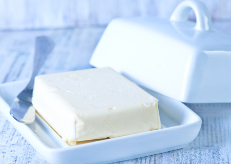 fresh butter on plate and on a table Stock Photo