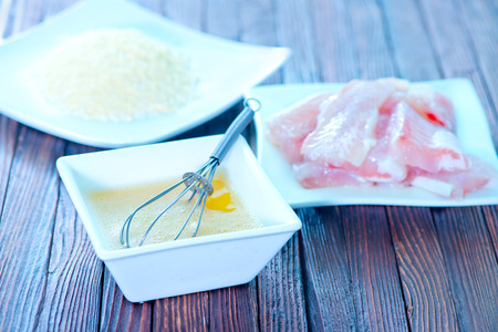 flour, raw egg and raw fish on a table photo