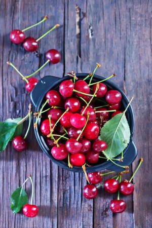 sour cherry: fresh cherry in bowl and on a table