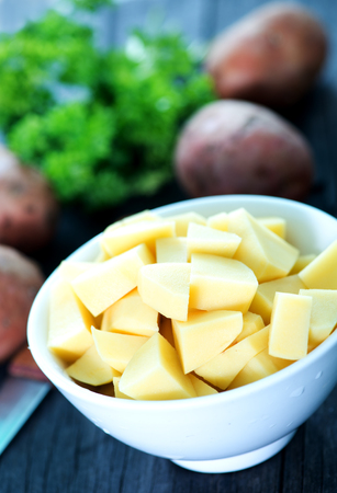 raw potato: raw potato in bowl and on a table