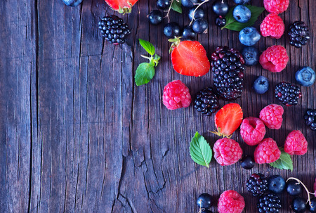 small basket: berries on the wooden table, mixed berries