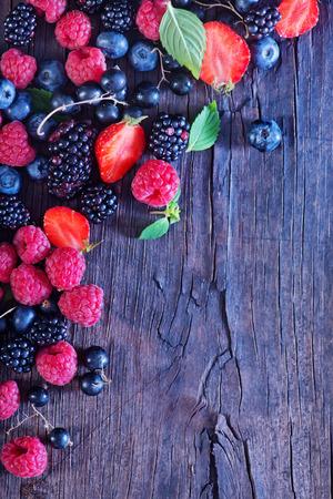 canastas con frutas: bayas en la mesa de madera, mezcla de bayas Foto de archivo