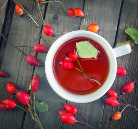 red cup: fresh tea with rosehip on a table