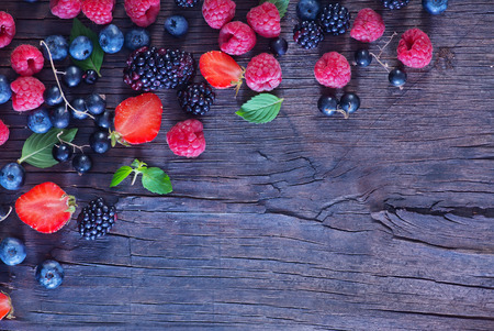 a background: berries on the wooden table, mixed berries