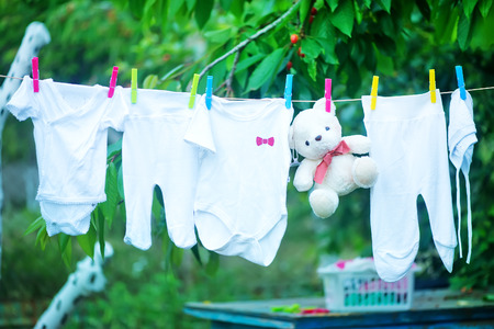 natural childbirth: baby clothes in garden, clear baby clothes Stock Photo