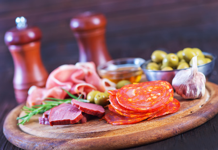 bri: salami, sausages and ham on the wooden board