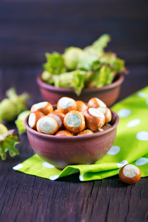 allergic ingredients: Filtered image of Hazelnuts in a wooden bowl on rustic background