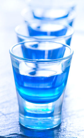 alcoholic drink: blue alcoholic drink into small glasses on a table Stock Photo