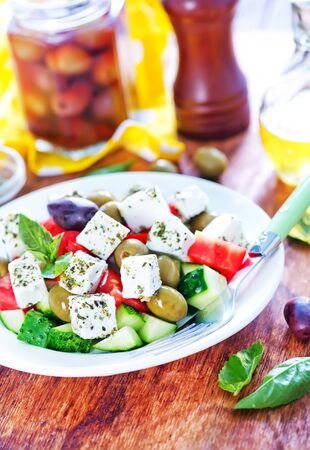 heathy diet: greek salad on plate and on a table