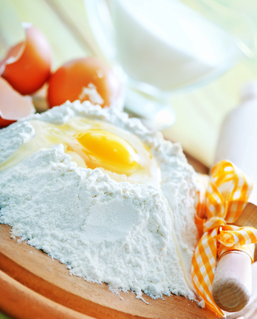 preperation: flour and raw eggs on the wooden board Stock Photo