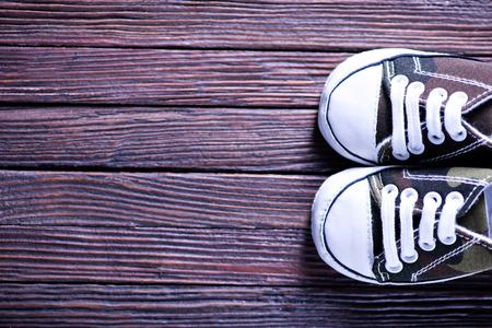 petit bonhomme: chaussures de bébé sur le fond en bois, chaussures sur une table