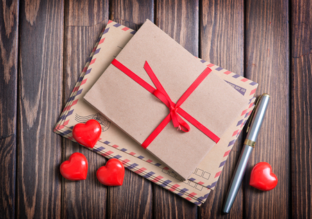 st valentin: envelopes and red hearts on the wooden table Stock Photo