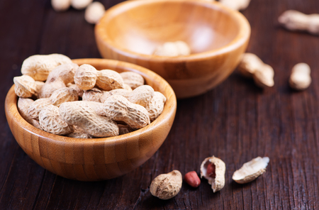 earthnuts: peanuts in bowl and on a table Stock Photo