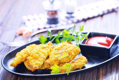 fishfinger: fried fish on plate and on a table