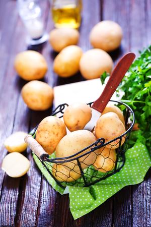 raw potato: raw potato and knife on the wooden table Stock Photo