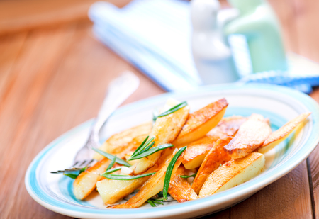 rosmarin: baked potato with rosemary on plate and on a table