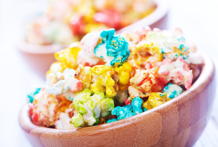 popcorn bowls: color popcorn in bowls and on a table Stock Photo