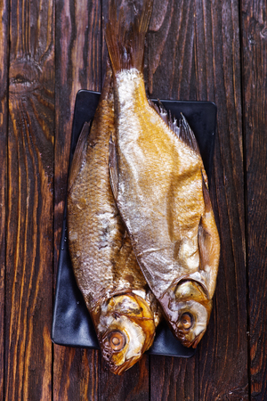 smoked fish on plate and on a table