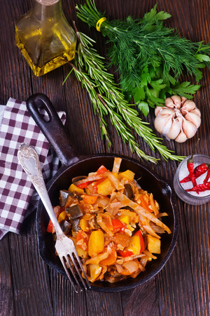 steel pan: fried vegetables in pan and on a table Foto de archivo