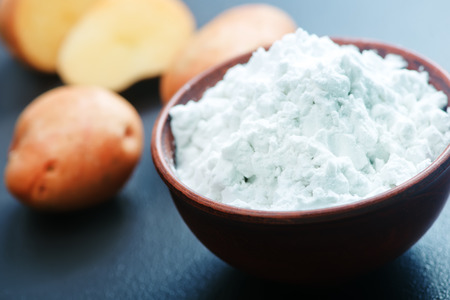 starch: potato starch in bowl and on a table Stock Photo