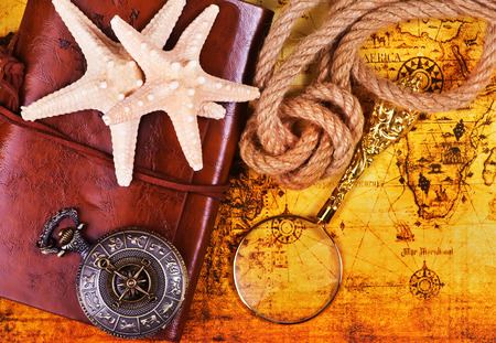 travel background, old notebook, loupe and compass on the map Stock Photo
