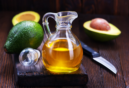 avocado oil in glass and on a table
