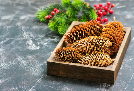 christmas decoration, cones and branch on a table