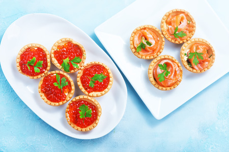 tartalets with salmon fish and caviar on a table