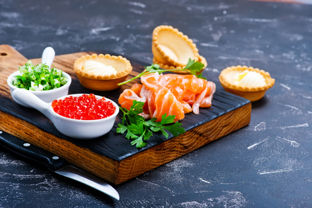 fresh food fish cake: tartalets with salmon fish and caviar on a table