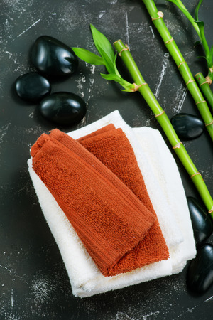 clear towels, black stones and bamboo on a table Stock Photo
