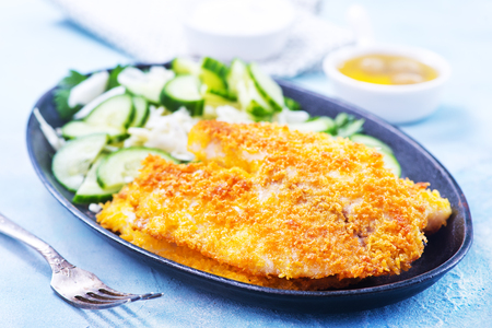 fried fish on plate and on a table