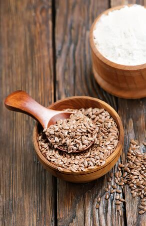 linseed: flax seed and flour on the wooden table Stock Photo
