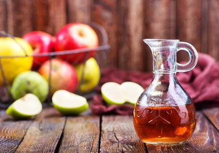 El vinagre de manzana en botella y en una mesa Foto de archivo