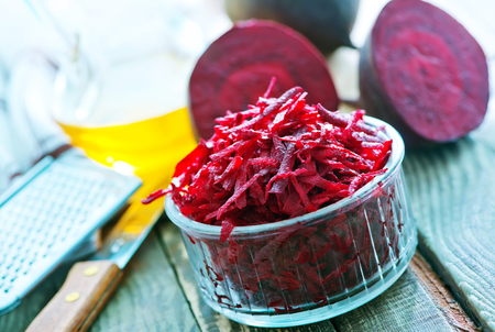 grated beet in bowl and on a table